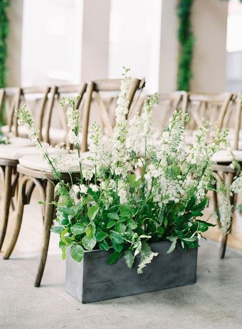 a concrete box with greenery and flowers for aisle decor