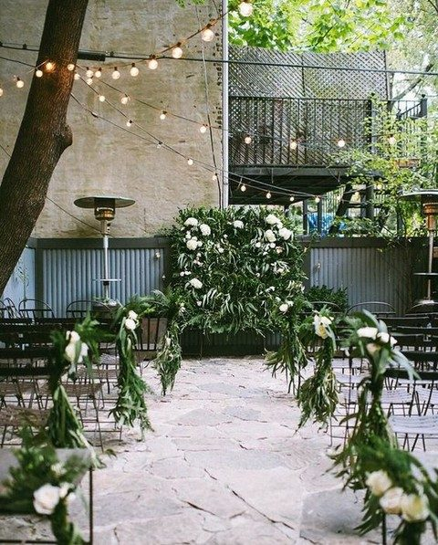 a greenery and flower wall backdrop and greenery and flower aisle decor