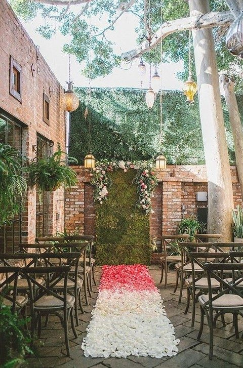 a moss wall backdrop and flower petals on the aisle