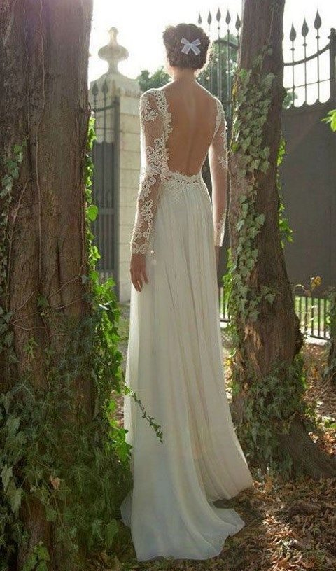 backless wedding dress with lace sleeves and a flowy skirt