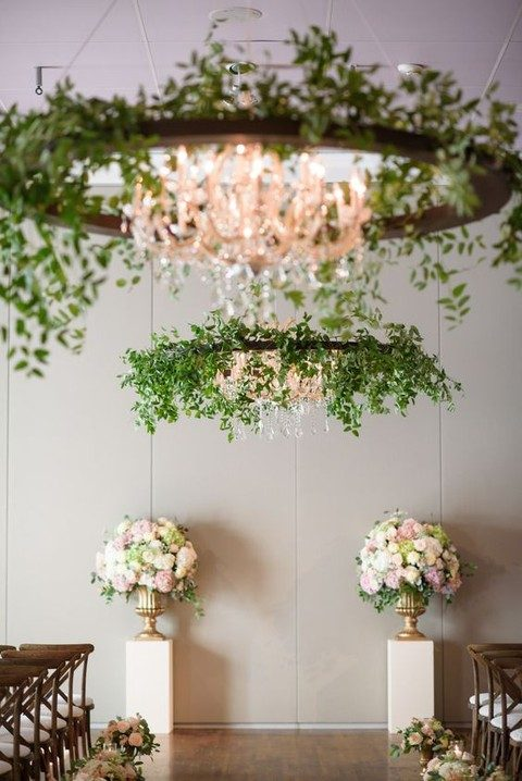 greenery covered chandeliers and flower decor for the ceremony spot