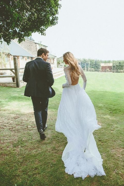 lace wedding gown with long sleeves and a flowy and airy skirt with a train