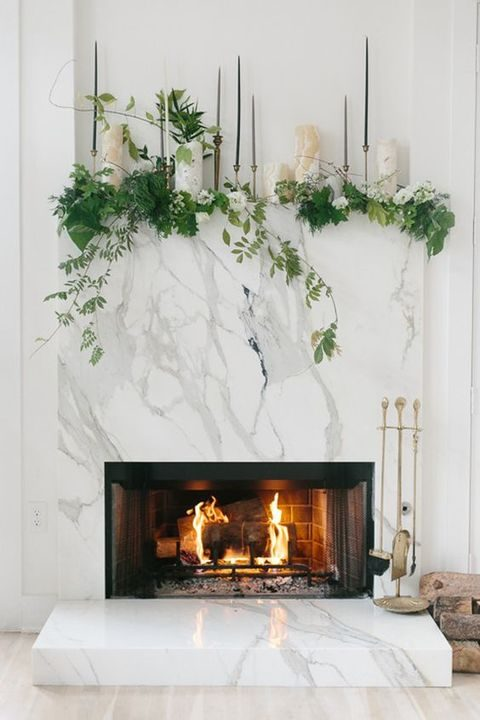 marble fireplace with greenery and candles as a wedding backdrop