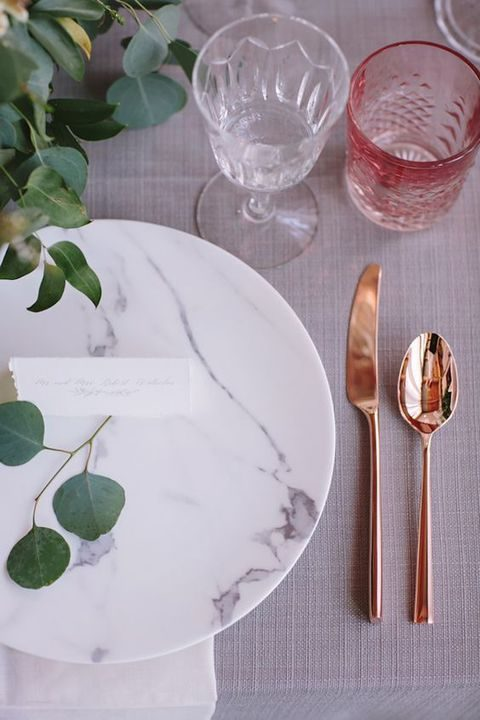marble plates, copper tableware and greenery