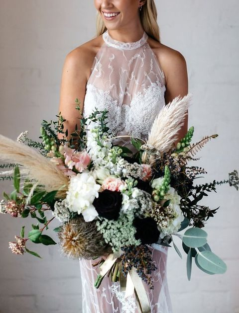 messy bridal bouquet with greenery, leaves, pampas and some dark flowers