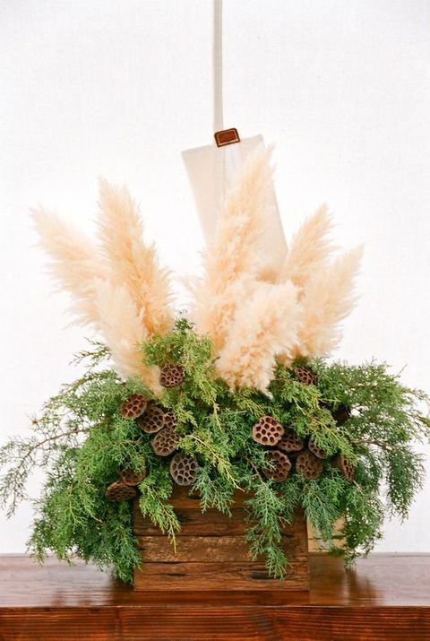 pampas, evergreens and lotus in a crate as a creative centerpiece