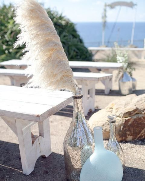 pampas grass in mercury glass bottles for a beach wedding