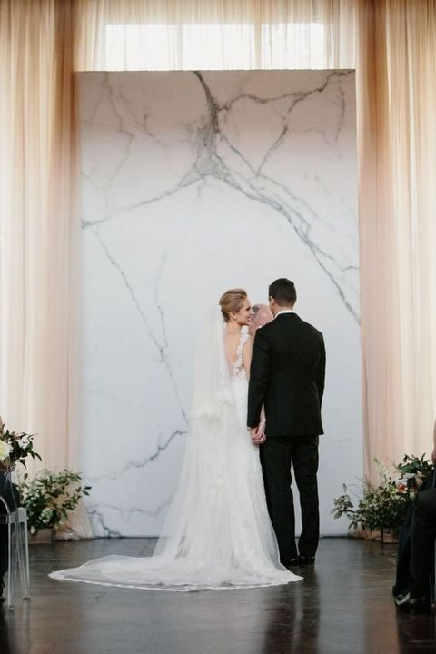 sleek marble ceremony backdrop is ideal for a modern wedding