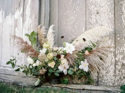 wedding centerpiece with pampas grass, neutral and bold flowers