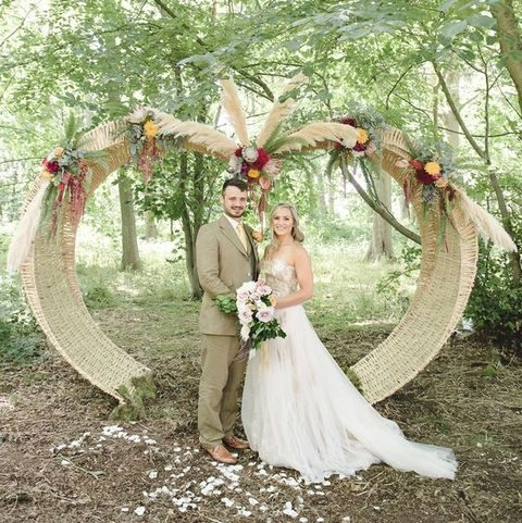 wicker arch decorated with flowers and pampas