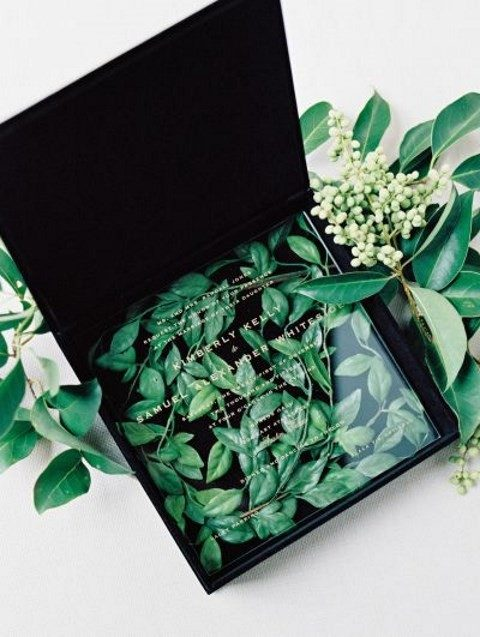 a black velvet box with fresh leaves and an acrylic invite