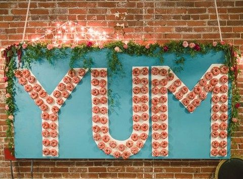 a blue wall with greenery and flowers and donuts displayed in the shape of the word YUM