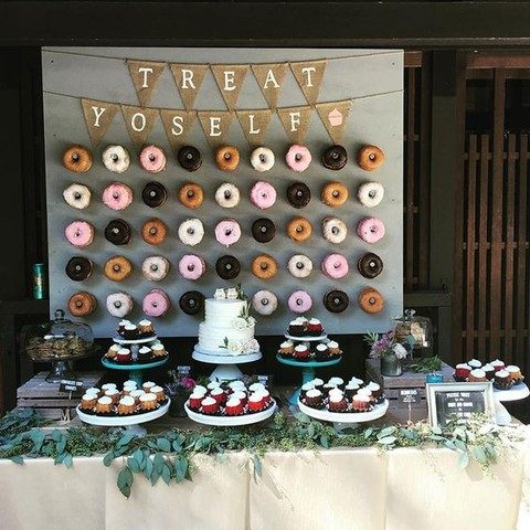 a dessert table with a donut wall decorated with a bunting
