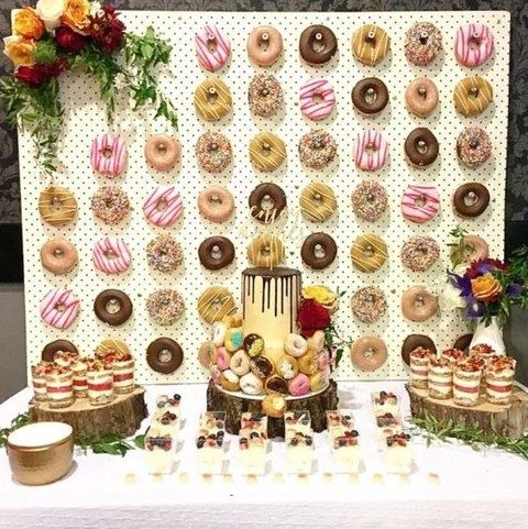 a dessert table with a glazed donut wall