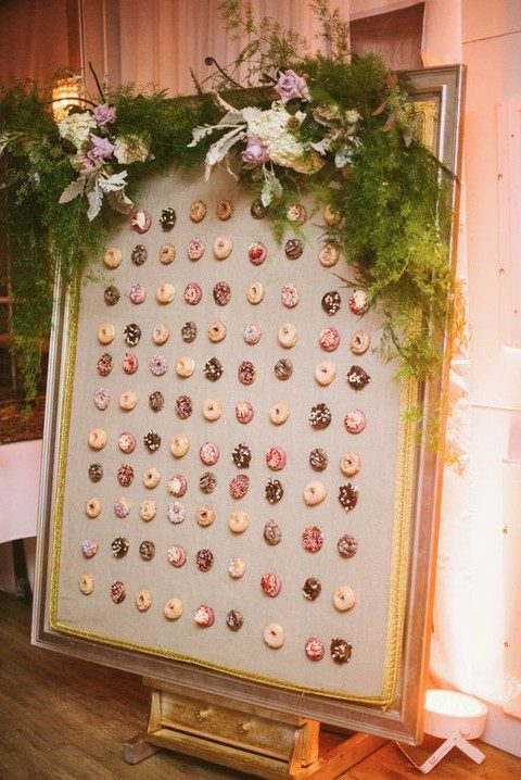a framed donut wall with greenery and flowers