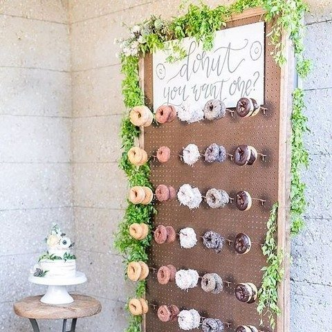 a pegboard wall with donuts decorated with greenery