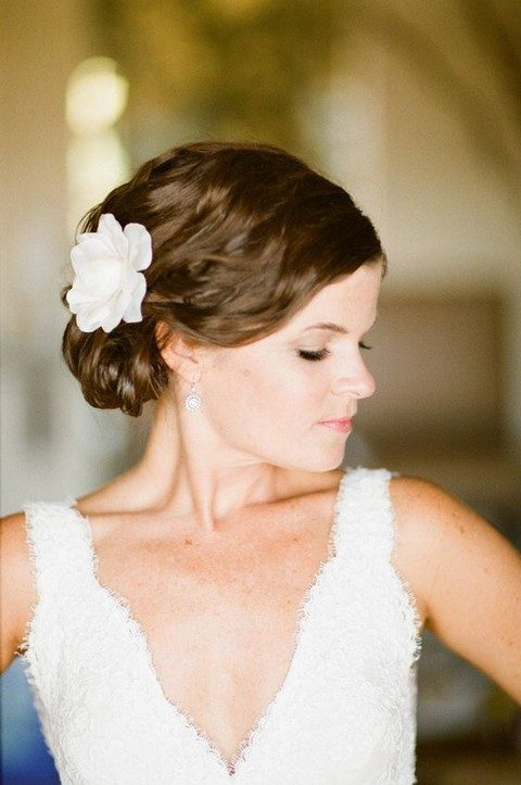 a side swept updo with a flower