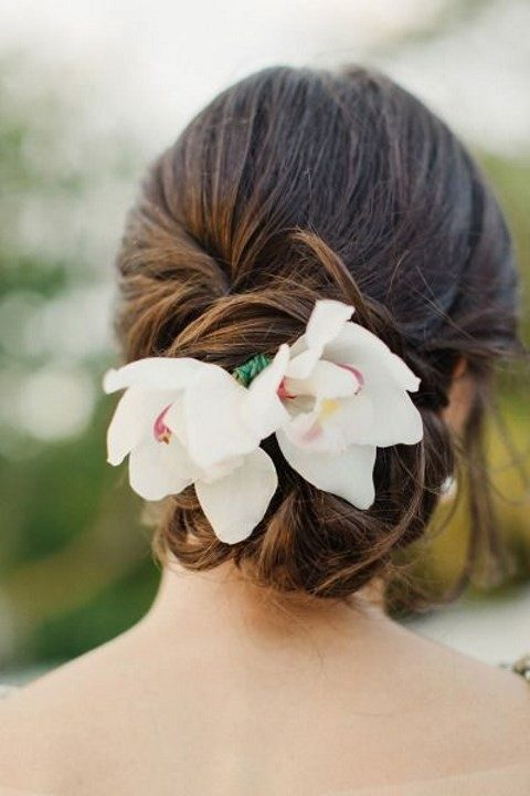 a stylish updo with white tropical blooms
