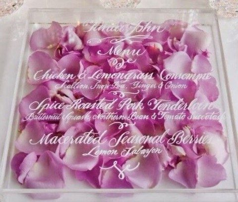 an acrylic wedidng invitation filled with rose petals