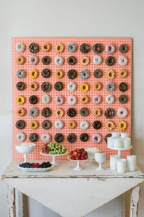 coral-colored pegboard wall with hooks for displaying donuts