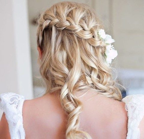 half up half down curly hair with a braid and flowers in it