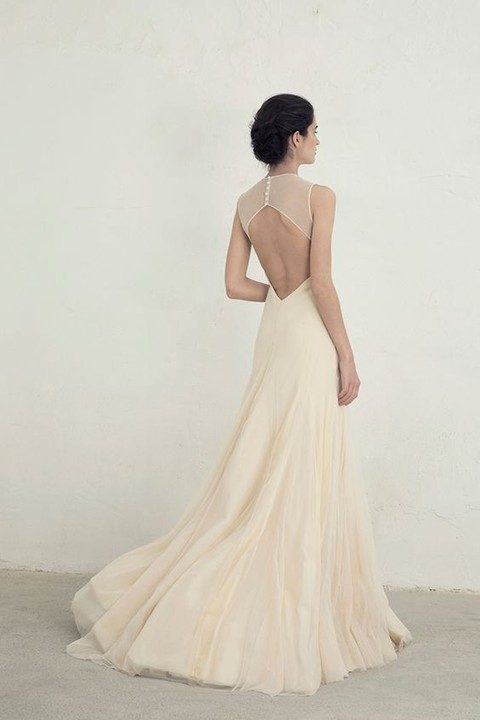 ivory tulle sleeveless gown with a cutout back and buttons on it