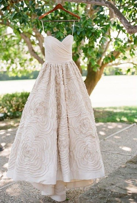 ivory wedding dress with a draped bodice and a floral skirt