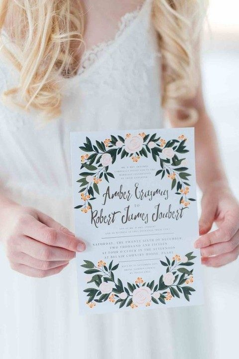 painted wedding invite featuring a green wreath and script style lettering