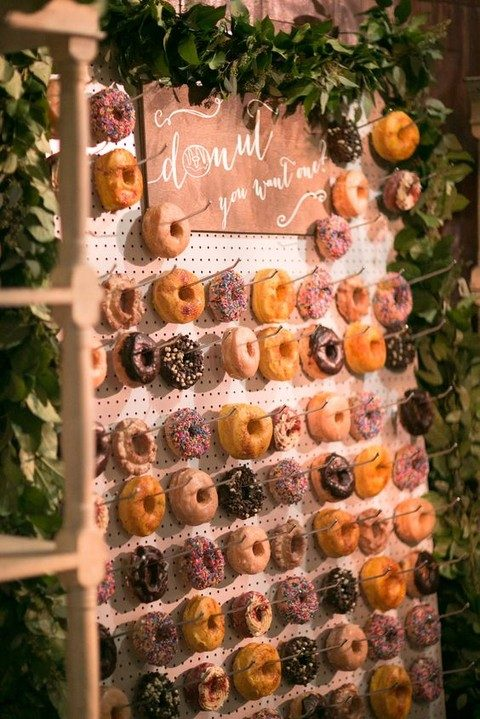 pegboard wall with greenery and a sign, lots of donuts on hooks