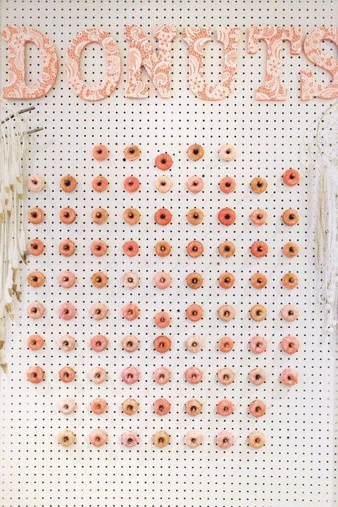 white pegboard wall with large lace letters and pink donuts