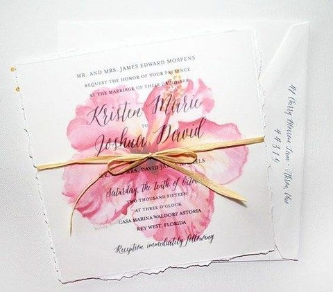 a rough edge and tropical flowers on the wedding invitations