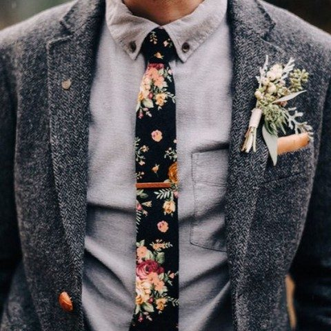 a tweed jacket, a grey shirt and a black floral tie