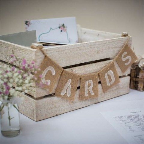 a whitewashed crate with a burlap banner