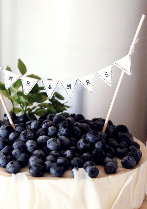 blueberry cheesecake topped with fresh berries and a banner