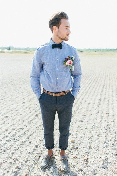 dark grey pants, a blue shirt, grey moccasins and a bow tie