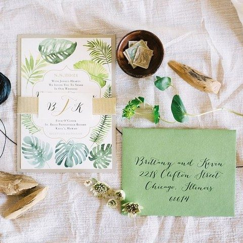 watercolor palm leaf wedding invites and a green envelope