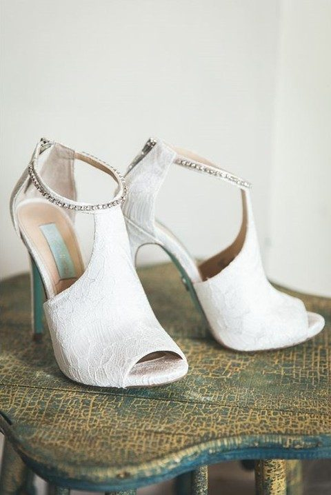 white lace wedding boots with peep toes and cutouts and a row of rhinestones
