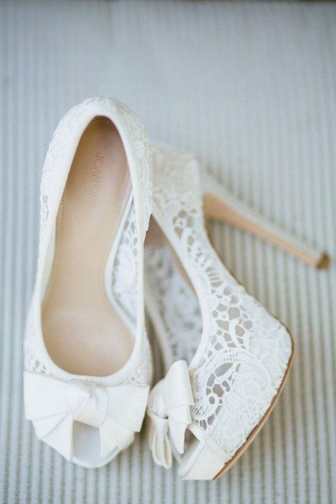 white lace wedding heels with peep toes and bows on them