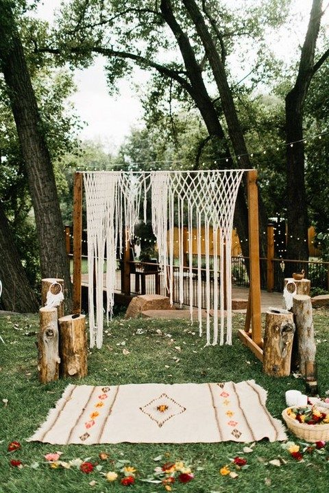 a boho ceremony space with a macrame hanging and a boho-inspired rug