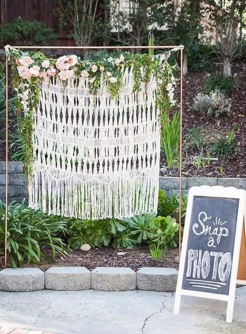 a macrame backdrop hung on copper tubing and with lush flowers and greenery