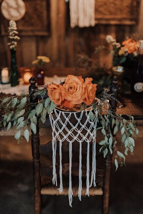 a macrame chair decoration with orange flowers and eucalyptus