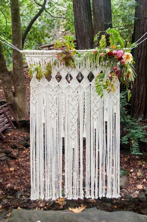 a macrame hanging with greenery and crystals for a wedding backdrop