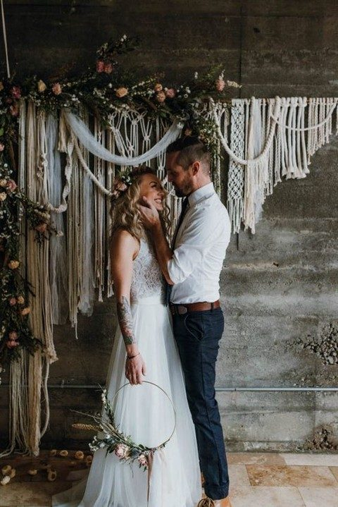 a macrame hanging with tulle and blush flowers and greenery