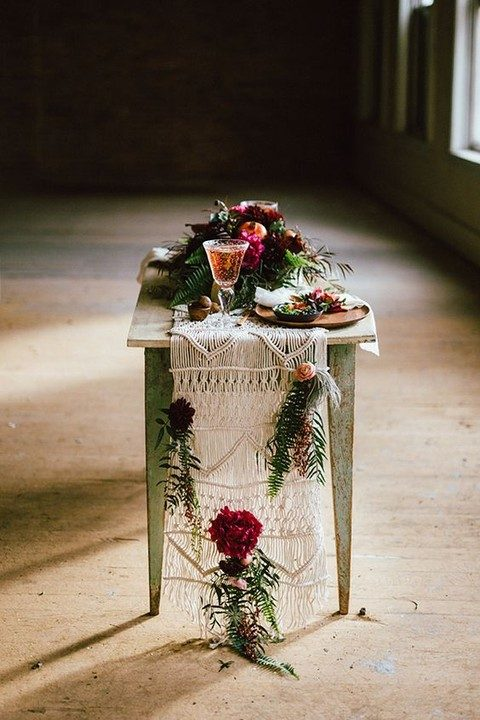 a macrame table runner with bold blooms interwoven