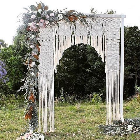 a macrame wedding arch with lush greenery and flowers