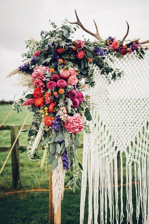 a macrame wedding backdrop with antlers with lush florals