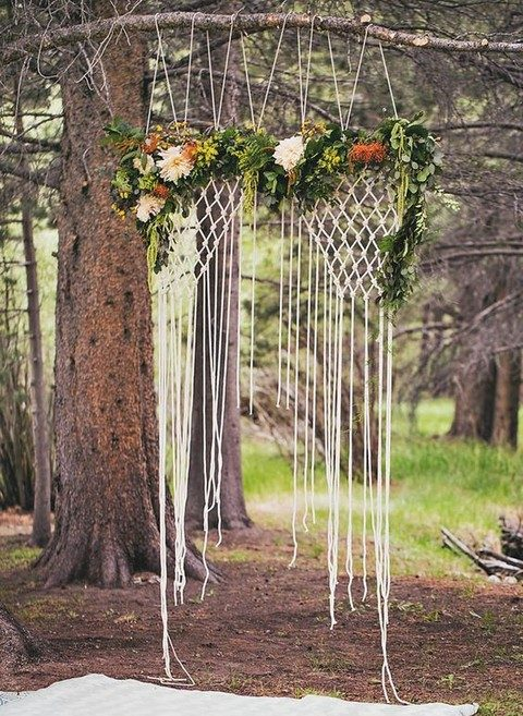 a macrame wedding backdrop with fresh greenery and flowers