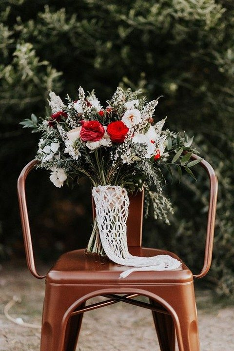 a white and red bridal bouquet with a macrame wrap and fringe