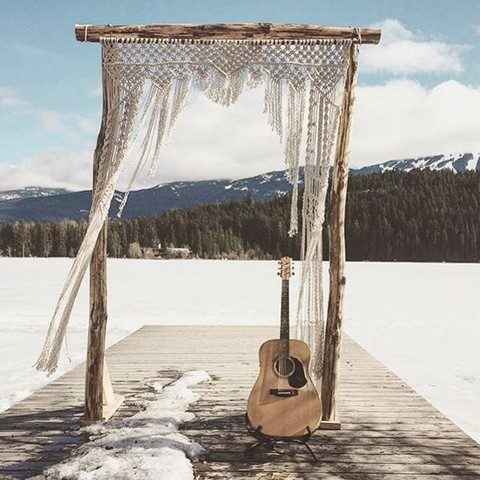 a wooden arch with a macrame hanging for an outdoor boho ceremony