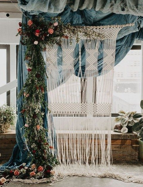 beautiful macrame backdrop with a lush floral and greenery garland